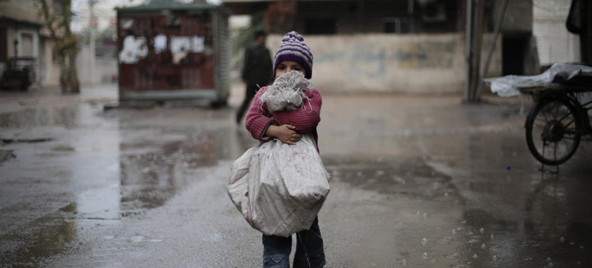 A child carries a bag of firewood she bought for her family in besieged east Ghouta, Syria.