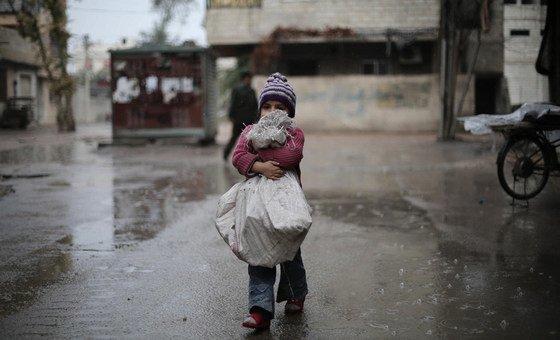 طفلة تحمل حطبا إلى عائلتها في الغوطة الشرقية، سوريا.