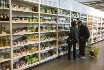 Customers in Rome, Italy, browsing products on sale inside an Italian gourmet food store.