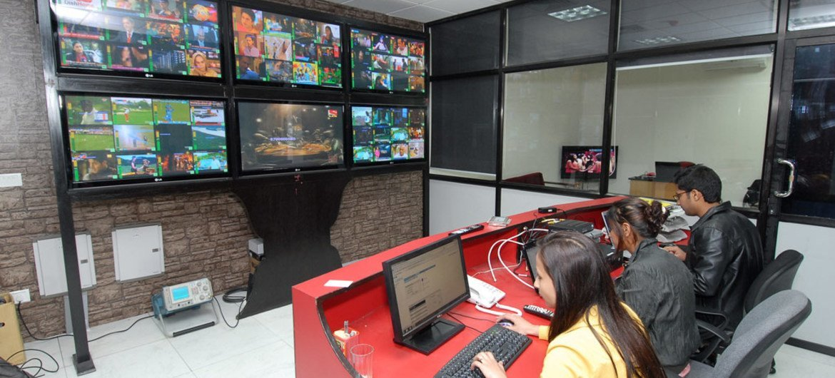 Young people monitor the transmission quality at a television broadcasting company in Nepal.
