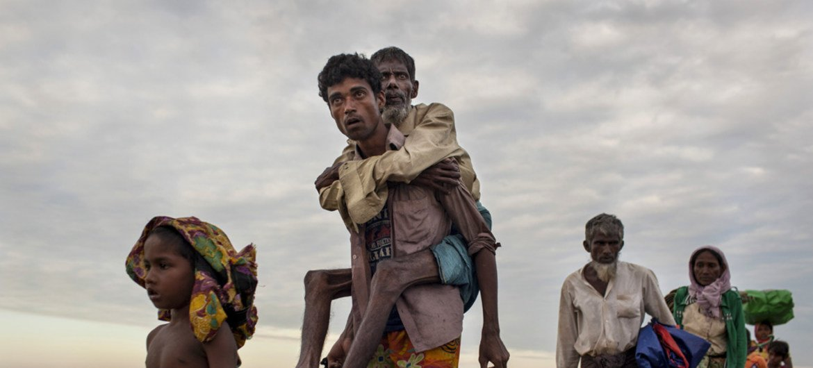 Rohingya refugees who crossed the Naf River, which demarcates the border between Myanmar and Bangladesh, on makeshift rafts made of logs, bamboo poles and jerrycans, walk along an embankment.