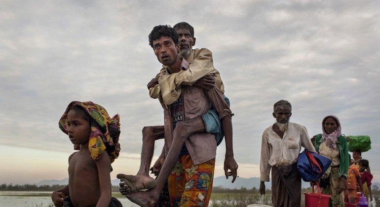 Refugiados rohingyas cruzan el río Naf para llegar a Bangladesh en balsas hechas de bamboo.