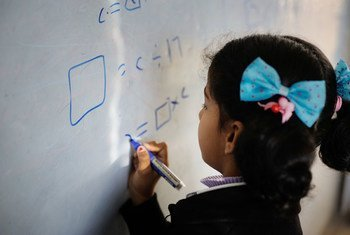 A young girl writes on a whiteboard during class at a school in Dohuk governorate, Iraq.