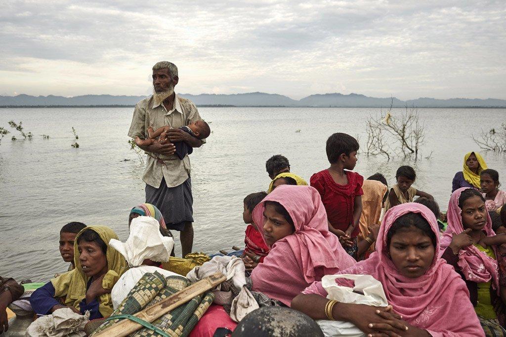 Un réfugié rohingya avec un nourrisson dans ses bras debout aux côtés d'enfants et de femmes sur un radeau de fortune après avoir traversé la rivière Naf, qui délimite la frontière entre le Myanmar et le Bangladesh.