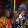 A mother waits with her children to receive food at an Internally Displaced Persons camp at Doolow, Gedo region, Somalia (June 2017).