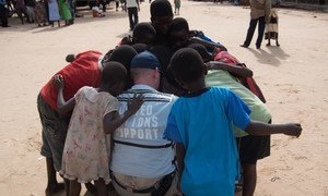 A member of the United Nations Disaster Assessment and Coordination (UNDAC) Team takes a moment to talk with children during the assessment after flooding in the southern part of Malawi in 2015. Credit: UNDAC.