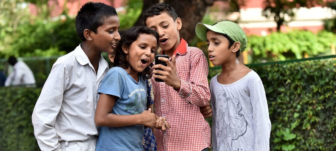 Children at St. Columba's School, Delhi, India, use a mobile phone