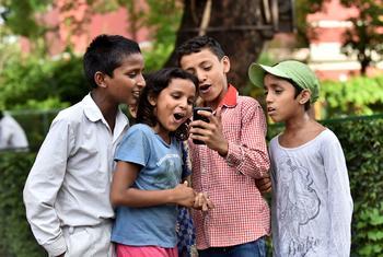 Des enfants à Delhi, en Inde, se servent d'un téléphone portable.