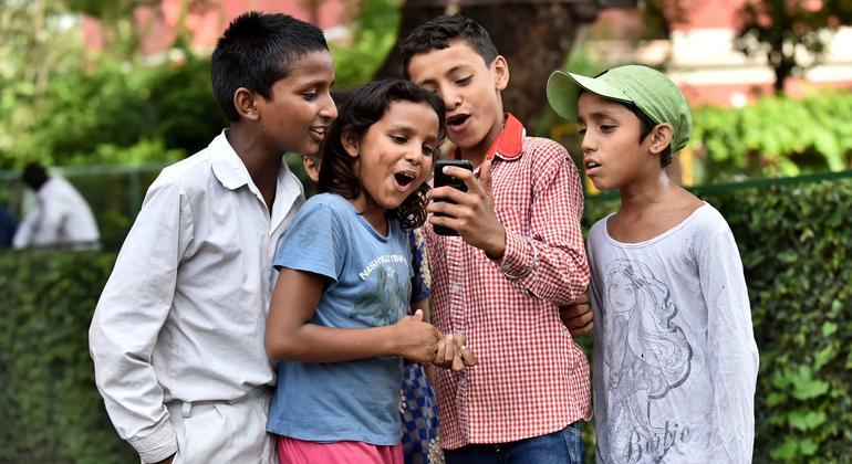 Niños en la Escuela San Columba en Delhi, India, toman fotos con su celular inteligente.