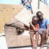 Dos hermanos sentados en lo que queda de su casa, que fue severamente dañana por el huracán Irma en Grand Turks, en las islas de Turcos y Caicos.