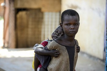 Un garçon porte sa jeune soeur sur son dos. Les deux enfants vivent dans la rue à Aweil, au Soudan du Sud. Photo : UNICEF / Rich