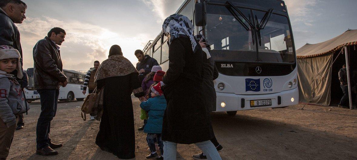 Migrants boarding a bus headed towards a processing center in Amman, the capital of Jordan.