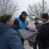 Dinu Lipcanu (centre, wearing baseball cap) Head of UNHCR's Mariupol field office in Ukraine, visits local residents whose houses have been damaged by artillery shelling in Avdiivka, Donetsk.