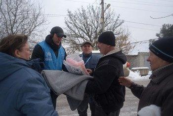 Mariupol, Ukraine: le chef du bureau local du HCR, Dinu Lipcanu (avec une casquette de baseball), rend visite aux résidents dont les maisons ont été endommagées par des tirs d'artillerie à Avdiivka, Donetsk.