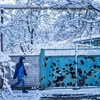A child walks past the front gate of a house damaged by shelling in Avdiivka, Donetsk Oblast in eastern Ukraine.