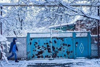 Подросток  идет по улице мимо ворот дома, поврежденных во время  обстрелом в Авдеевке в Донецкой области на востоке Украины. Фото: ЮНИСЕФ / Гилбертсон