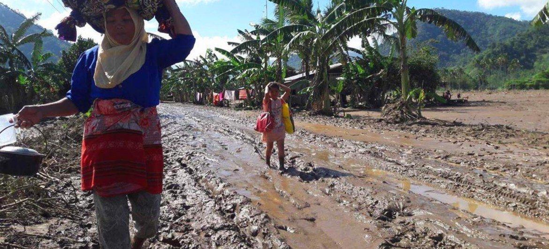 """一名妇女和一名小孩在菲律宾北棉兰老岛北拉瑙市被热带风暴""""天枰""""毁坏的道路上行走。图片: 联合国难民署/J. Pangalian"""
