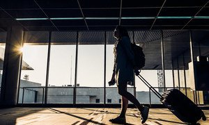Silhouette of young girl walking with luggage walking at airport terminal window at sunrise.