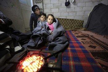Сирийская семья  пытается укрыться от холода в  недостроенном  здании  в  одном из районов в Хомсе. Фото ЮНИСЕФ/Санадики