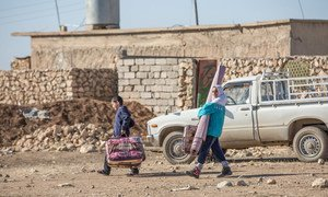 Iraqi returnee family in the village of Wana, west of the city of Mosul, carry away relief kit supplied by the UN International Organization for Migration (IOM).