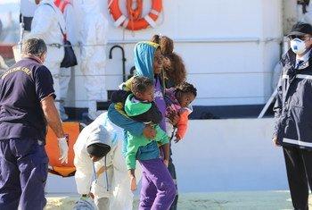 Une femme avec deux bébés débarque d'un bateau qui l'a secourue en Méditerranée entre la Libye et l'Italie (archives).