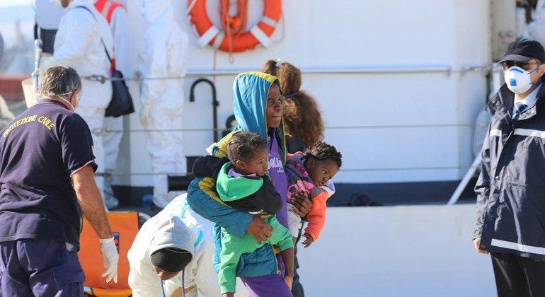 Una mujer lleva a sus dos bebés mientras desembarca del barco que la rescató cuando intentaba cuzar el Mediterráneo de Libia a Italia.