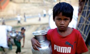A seven-year-old Rohingya girl carries a pot of water to her family's makeshift shelter after filling it at a hand operated water pump at the Bormapara makeshift settlement in Ukhia, Cox's Bazar, Bangladesh.