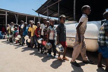 Niños desplazados internos en Mogadishu, Somalia esperan en línea para recibir comida del Programa Mundial de Alimentos.