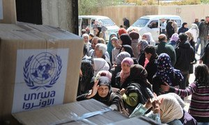Beneficiaries queue for food assistance at the UNRWA distribution centre in Sahnaya, Damascus in Syria.