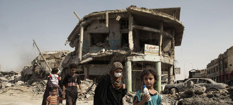 Mulheres e crianças andam em meio à destruição em Mossul, no Iraque