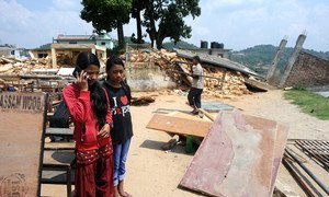 Two girls speak to a psychologist using a mobile phone in rural sindhupalchowk, Nepal. In the background, a house lies in ruin, destroyed by the devastating 2015 earthquakes in country.