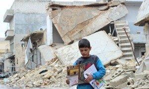 Un enfant porte des manuels distribués par des volontaires de l'UNICEF à la suite d'une séance d'information sur les engins non explosés à Alep, en Syrie. Photo UNICEF/Al-Issa