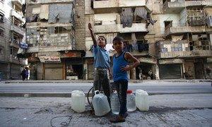 Un garçon âgé de 9 ans et son frère âgé de 6 ans attendent de remplir des jerrycans à une source d'eau dans l'est d'Alep, en Syrie. Photo UNICEF/Zayat