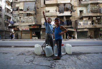 A 9-year-old boy and his brother, 6, wait for their turn to fill the empty jerry cans from a local water well in eastern Aleppo, in Syria.