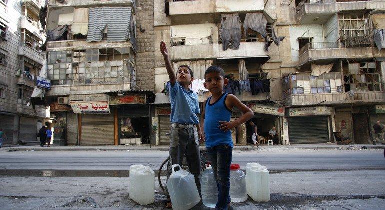 Dos hermanos esperan su turno para llenar bidones con agua potable en Alepo, Siria.