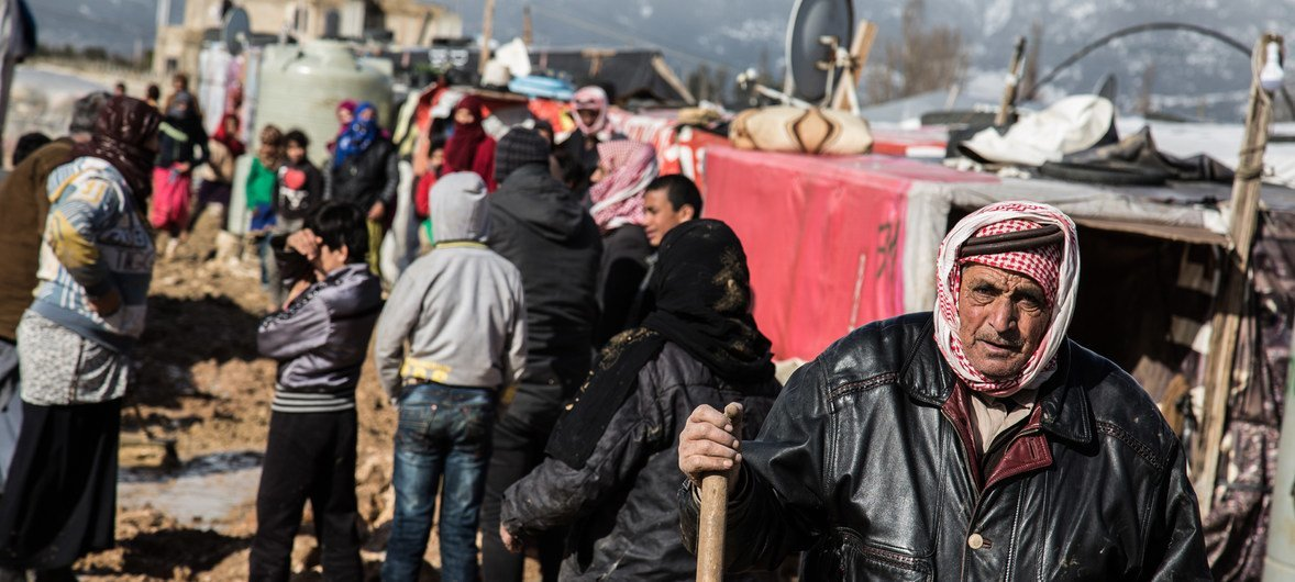 Syrian refugees gather outside their shelters following a winter storm which brought rain and snow, at an informal settlement in Haoush Harime, in Bekaa Valley, Lebanon.