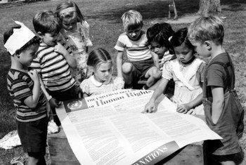 Un grupo de niños lee la Declaración Universal de los Derechos Humanos en un jardín de niños.