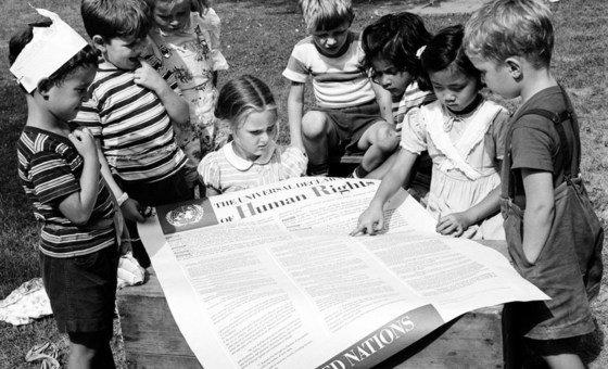 Un grupo de niños lee la Declaración Universal de los Derechos Humanos en un jardín de infancia.