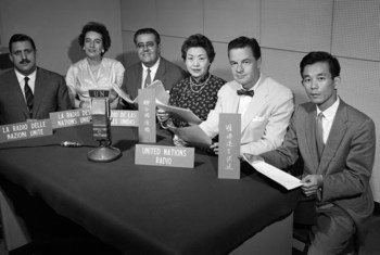 Some of the officers of the UN Radio Service in 1960 with signs indicating the languages in which they broadcast.