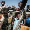 Des enfants se rassemblent à un point d'eau sur le site de Moni pour les personnes déplacées à Kalemie, en République démocratique du Congo. Le site accueille plus de 20.000 personnes.