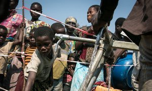 Children gather at a water point at Moni site for internally displaced persons in Kalemie, Democratic Republic of the Congo, hosting more than 20,000 people. Photo: OCHA/Ivo Brandau