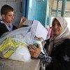 一名巴勒斯坦难民妇女在加沙的近东救济工程处汗尤尼斯分配中心获得粮食援助。