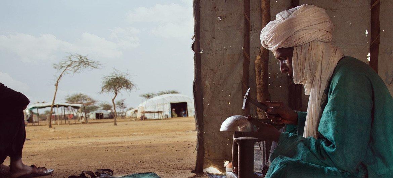 一位马里难民在根据工作计划培训项目接受缝纫训练