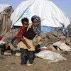 An 8-year-old girl carrying her 2-year-old brother at a settlement for persons displaced by conflict in Yemen..