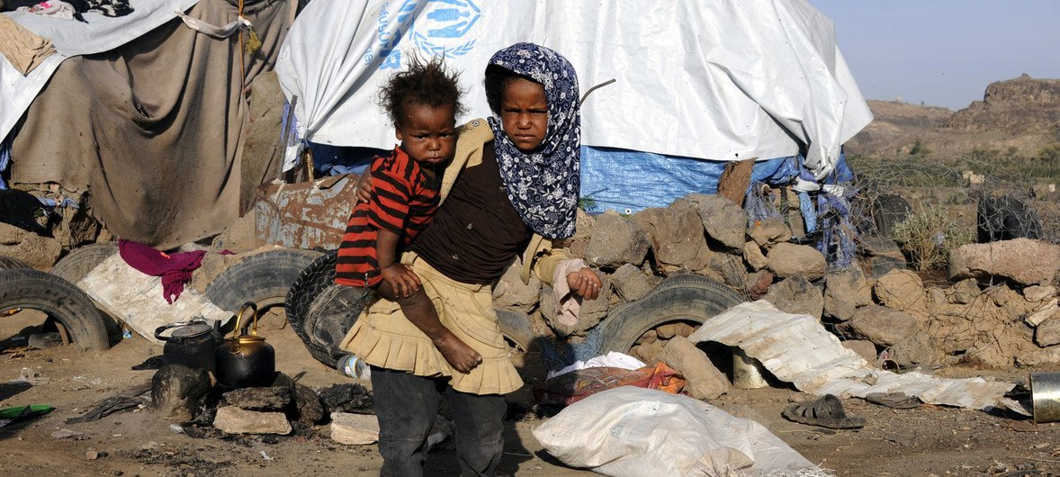 Rahaf Ali Bedaish, 8, carries her little brother Ahmed, 2, outside their tent at the Dharawan settlement. They have been displaced from Taizz governorate since the beginning of the conflict.