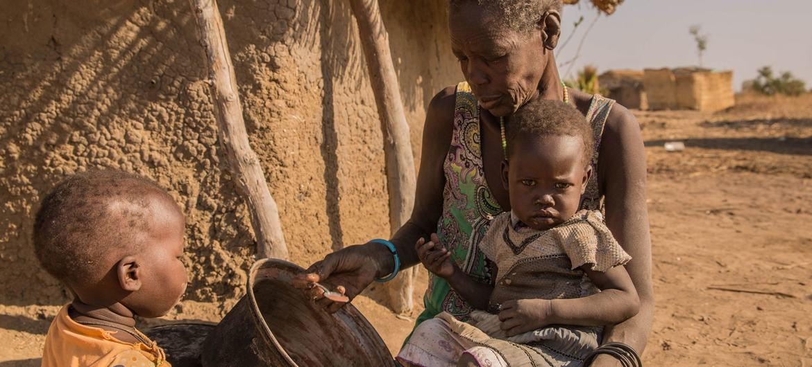 A mother giving sorghum porridge to her children. A growing number of children in South Sudan's Northern Bahr el Ghazal and Warrap have only one meal per day.