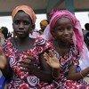 Deux jeunes filles au Sénégal applaudissent lors d'une célébration de l'abandon de la mutilation génitale féminine par plusieurs villages des environs.