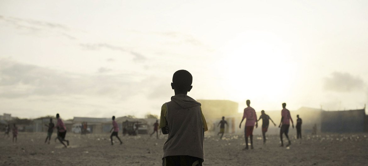 UN Photo/Tobin Jones A young child looks on as older boys play football next to a camp for internally displaced persons (IDP) in Mogadishu, Somalia.