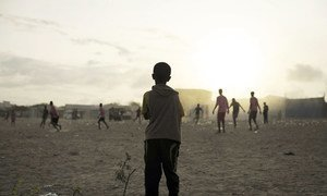 A young child looks on as older boys play football next to a camp for internally displaced persons (IDP) in Mogadishu, Somalia.