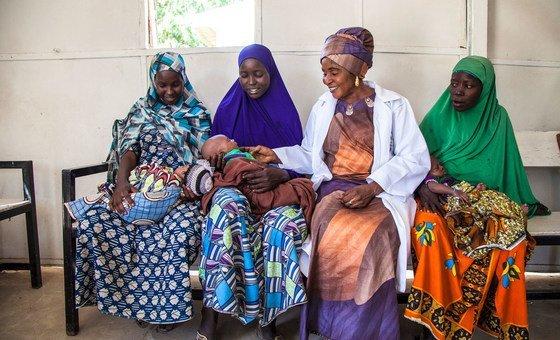 Grupo de mães falam com parteira Amina Shallangwa na Nigéria.